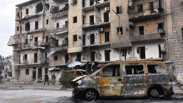 Syrian government forces walk past destroyed buildings in the former rebel-held Ansari district in the northern Syrian city of Aleppo on December 23, 2016 after regime forces retook control of the whole embattled city.(AFP Photo)