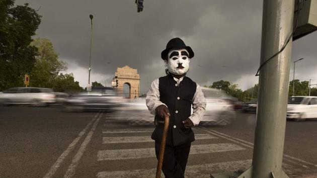 Monu, 52, is a tourist attraction in the lawns of India Gate. He is less than three feet and makes a living by posing as Charlie Chaplin. He charges Rs 10-Rs 20 for every selfie shot with him by tourists but sometimes people mock him and call him names.(Raj K Raj/ HT Photo)