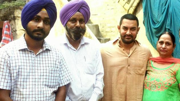 Omkarjot Singh with his parents and Aamir Khan during shoot of Dangal movie at his home in Kila Raipur in Ludhiana on Thursday.(JS Grewal/HT Photo)