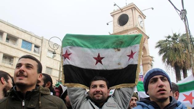 Dozens of Syrians take part in a small gathering calling for the fall of the regime on Friday in the northwestern city of Idlib.(AFP)
