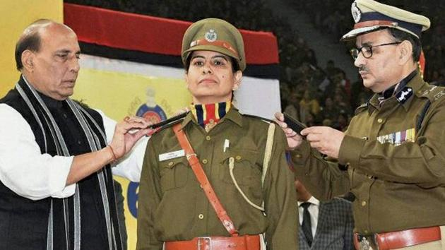 Union home minister Rajnath Singh (left) and Delhi Police commissioner Alok Kumar Verma (right) add stars to the uniform of a woman police officer on Saturday.(PTI Photo)