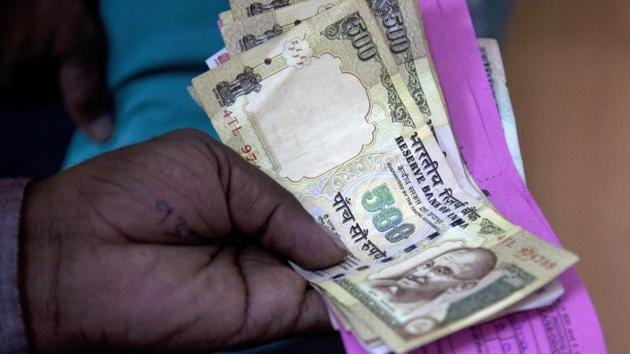 A person gives discontinued currency notes for depositing in a bank at Hyderabad.(AP File Photo)