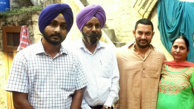 Omkarjot Singh with his parents and Aamir Khan during shoot of Dangal at his home in Kila Raipur in Ludhiana. (HT Photo)