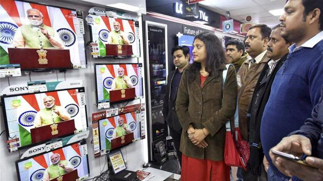 People watching live telecast of Prime Minister Narendra Modi's speech at an electronic shop in Patna on Saturday.(PTI)