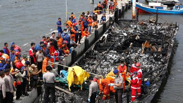 Police and rescue workers search a boat for victims at Muara Angke port in Jakarta, Indonesia.(REUTERS)
