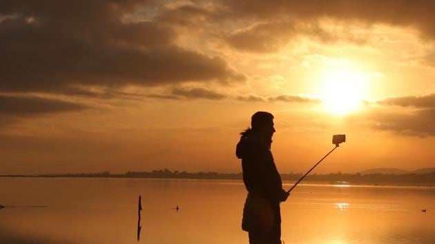 A person holds a selfie stick as the sun sets over a body of water in the Camargue on New Years Eve(AFP Photo/Representative Image)