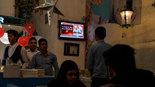 """Prime Minister Narendra Modi is seen on the television inside a restaurant as he address the nation on December 31. Modi had asked banks to """"keep the poor, the lower middle class, and the middle class at the focus of their activities"""" and to act with """"public interest"""" in mind.(AFP)"""