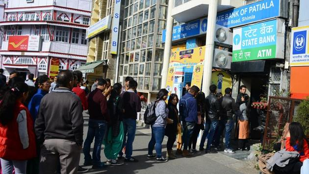 People stand in a queue outside an ATM in Shimla. With restrictions on cash withdrawal , a substantial portion of people's transactions should be carried out through cashless transactions, which would force them to become tax-compliant in the future.(HT Photo)