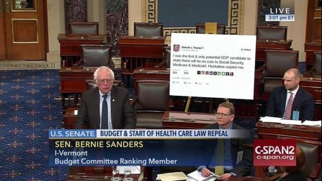 TV screengrab of Bernie Sanders speaking at the US Senate. Behind him a printout of tweet by Donald Trump(Photo: Gizmodo)