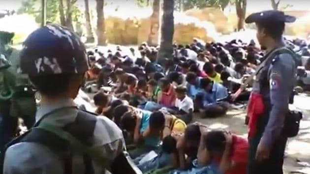 Screengrab from a video, originally taken by a Myanmar constable, shows policemen standing guard around Rohingya minority villagers in Kotankauk village during a police area clearance operation on November 5, 2016.(AFP file photo)