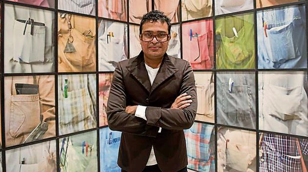 Artist Jitish Kallat with his work, The Cry of the Gland (2009), a study of shirt pockets and their contents.(Saumya Khandelwal/HT PHOTO)