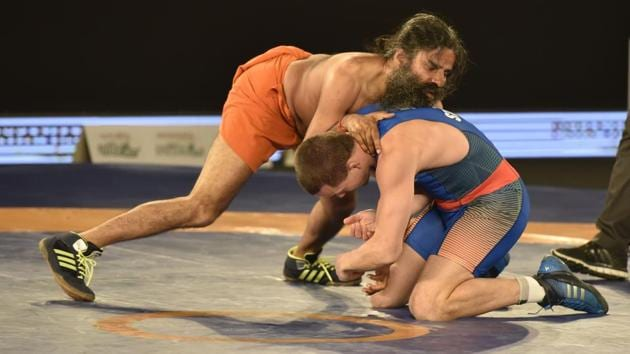 Baba Ramdev displayed his wrestling skills as he went head-to-head with 2008 Olympic silver medalist Andriy Stadnik in a promotional bout of the 2017 Pro Wrestling League (PWL).(Virendra Singh Gosain/HT PHOTO)