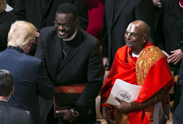President Donald Trump greets Bishop Harry Jackson of the Hope Christian Church in Maryland at an interfaith prayer service at the Washington National Cathedral. At right is Narayanachar L Dialakote of the Sri Siva Vishnu Temple in Maryland.(NYT Photo)