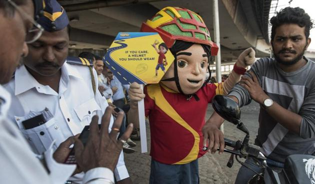 Traffic policemen, accompanied by a mascot of Shiva — a superhero from an animated TV show — catch a biker for not wearing a helmet, at Bandra on Tuesday.(Satish Bate/HT)