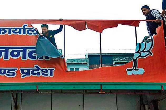 A BJP rebel supporter damages a hoarding at the party office in Dehradun.(Vinay Santosh Kumar/HT Photo.)