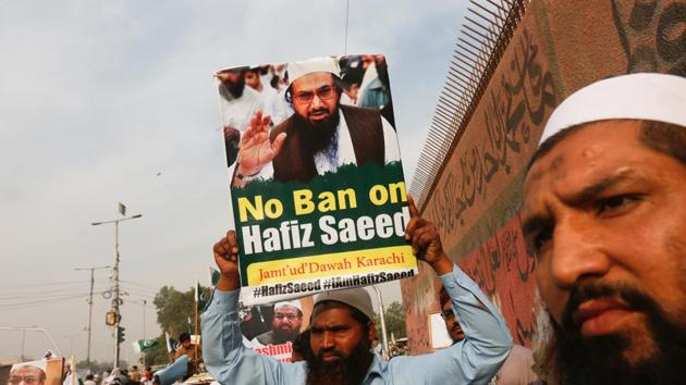 A supporter of Jamaat-ud-Dawa (JuD), carries a sign with others as they listen the speech of leaders (unseen) to condemn the house arrest of Hafiz Muhammad Saeed, chief of (JuD), during a protest demonstration in Karachi, Pakistan.(Reuters Photo)