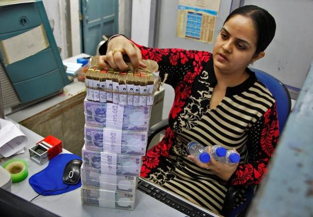 A cashier stacks currency notes inside a bank in Chandigarh, India, November 19, 2016. REUTERS/Ajay Verma/File Photo