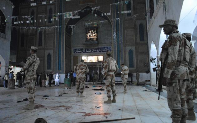 Pakistani paramilitary soldiers stand alert after the deadly suicide attack at the shrine of Lal Shahbaz Qalandar in Sehwan on Thursday.(AP)