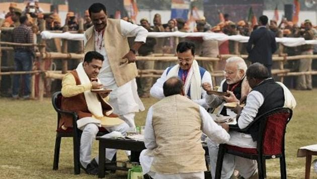 Prime Minister Narendra Modi seen having lunch with Sunil Bansal (in brown jacket) and a few other party workers at a meeting in Varanasi late last year.(File photo/ PTI)