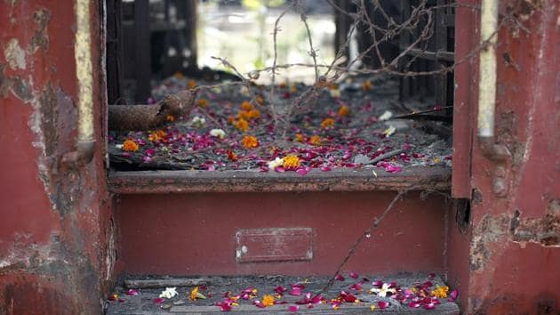 Flower petals scattered by the relatives of Godhra riots victims pictured at the doorsteps of a train carriage, that was set on fire in 2002, during the commemoration of the 12th anniversary of Godhra riots at Godhra, Gujarat(REUTERS)