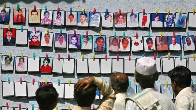 Survivors look at the pictures of the Godhra riots victims at a photo-exhibition held to commemorate its 10th anniversary in Ahmedabad, February 27, 2012.(REUTERS)