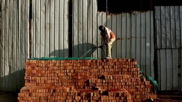 A worker waters a stack of bricks at a construction site in New Delhi. India's economic growth slowed marginally to 7% in October-December from 7.4% in the previous quarter after the controversial ban on high-value banks notes in November.(AFP)