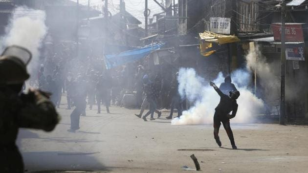 A Kashmiri youth throws stones during clashes with police and paramilitary soldiers in downtown area of Srinagar, on March 3, 2017. Police fired dozens of tear smoke shells and fired pellets in the air to disperse the crowds.(Waseem Andrabi / HT Photo)