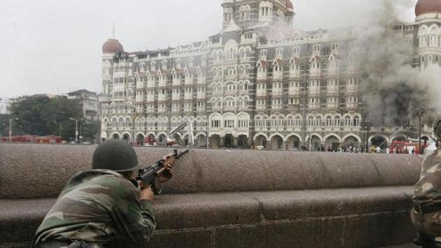 Soldiers take up position during a gun battle at the Taj Mahal hotel (seen in the background) in Mumbai in this November 29, 2008 file photo.(REUTERS)