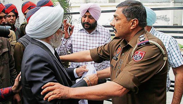 Sarabha Nagar SHO arguing with lawyer Bhupinder Singh who was stopping Ludhiana Improvement Trust officials from sealing the community centre in BRS Nagar, Ludhiana, on Tuesday.(JS Grewal/HT)