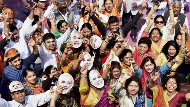 BJP supporters celebrate the party's victory in the Uttar Pradesh assembly elections wearing masks of Prime Minister Narendra Modi in New Delhi on Saturday.(PTI photo)