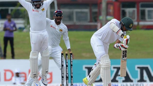 Soumya Sarkar is bowled by Asela Gunaratne as Sri Lanka players celebrate on fifth day of the first Test against Bangladesh.(AFP)