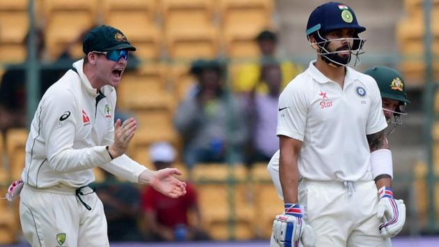 Virat Kohli looks on as Steve Smith celebrates his dismissal on Day 1 of the second Test at Chinnaswamy Stadium in Bangalore.(PTI)