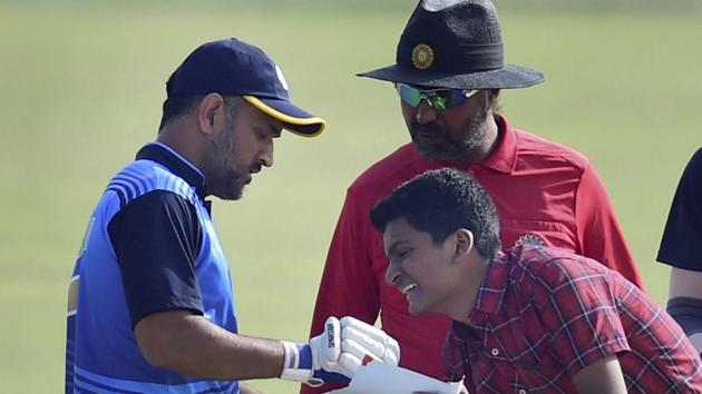 Jharkhand cricket team captain MS Dhoni obliges a young fan during the Vijay Hazare trophy quarterfinal match against Viharbha cricket team in New Delhi on Wednesday.(PTI)