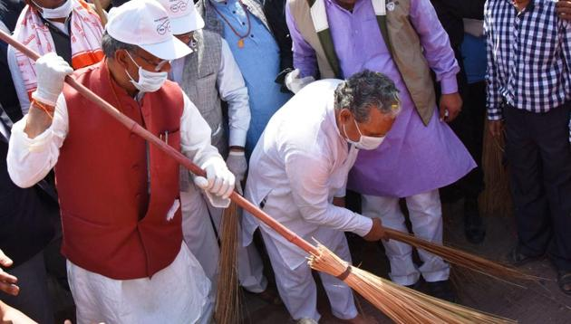 Chief minister Trivendra Singh Rawat wields a broom during the Swachh Bharat drive in Dehradun on Monday.(Vinay Santosh Kumar/HT)