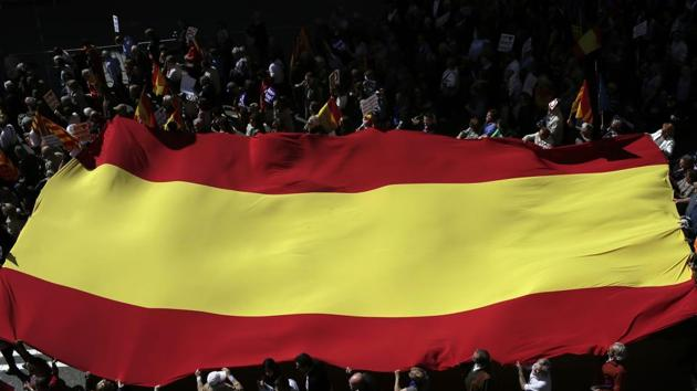 People hold a Spanish flag as they protest the regional Catalan government's push to break away from the rest of Spain, in Barcelona, on Sunday.(AP Photo)