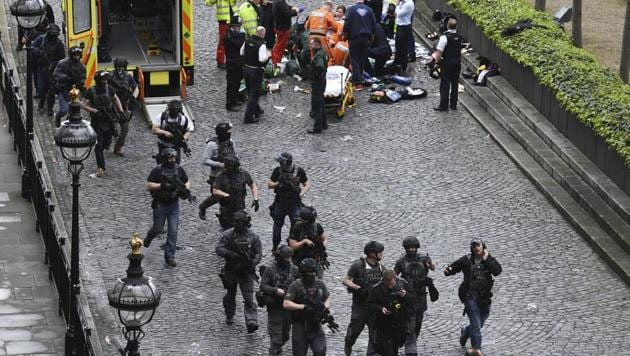 Armed police walk past emergency services attending to injured people on the floor outside the Houses of Parliament, London, on March 22, 2017.(AP)