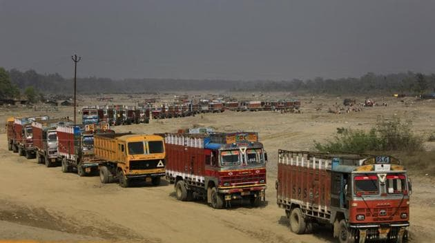 The trucks lined up to collect sand and stone from a tributary of river Ganga in Uttarakhand. Most of the minerals from the river bed being lifted are said to be illegal and locals claims the activity has increased in the last few months since the state went to elections.(Vipin Kumar/Hindustan Times)