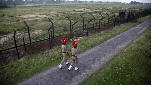 Border Security Force personnel patrol near a fence on the India- Bangladesh border at Thakuranbari village, in Assam.(AP File Photo)