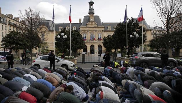Hundreds of Muslims pray on the street in front of the town hall plaza, seen behind, in the Paris suburb of Clichy la Garenne, Friday, March 31, 2017.(AP Photo)