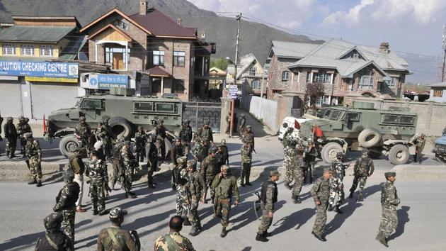 Army and paramilitary personnel gather near the site of a militant attack in Sempora area on the outskirts of Srinagar on Monday.(Waseem Andrabi/ HT Photo)