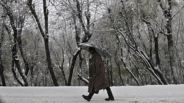 A man walks during snowfall on the outskirts of Srinagar.Kashmir Valley reeled under unprecedented rain and snow that swelled rivers and inundated vast areas.(Waseem Andrabi /HT Photo)