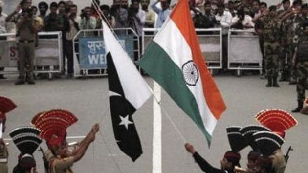 Pakistani rangers (in black uniforms) and Indian Border Security Force (BSF) officers lower the national flags during a daily parade at the Wagah border. Pakistan has charged Kulbhushan Jadhav for his alleged involvement in espionage and sabotage against Pakistan as a Research and Analysis Wing (R&AW) agent. He was arrested on March 3 last year in Balochistan.(Reuters File Photo)
