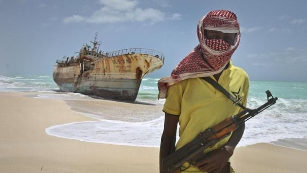 In this file photo, a masked Somali pirate stands near a Taiwanese fishing vessel that washed up on shore after the pirates were paid a ransom and released the crew, in the once-bustling pirate den of Hobyo, Somalia.(AP)