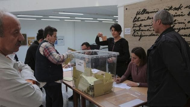 A member of an electoral committee holds a ballot during a counting procedure inside a polling station in Ankara, Turkey, on Sunday, April 16, 2017.(AP Photo)
