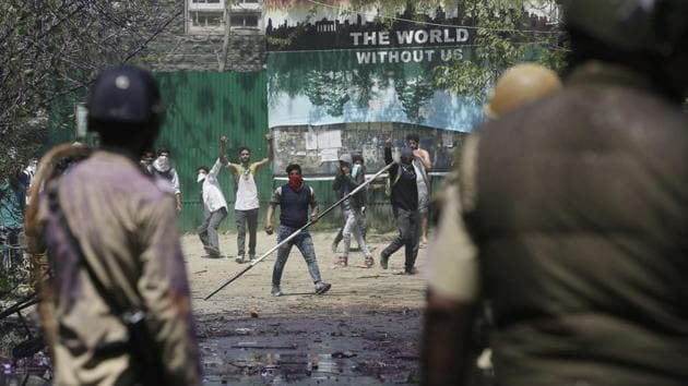 A Kashmiri student holds an iron rod as others throw stones at policemen as they clash in Srinagar on Monday.(AP)
