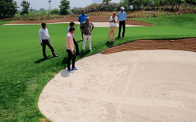 Forest department officials check for animal footprints at the DLF Golf Course following leopard sighting reports that spread panic in the upscale area.(Parveen Kumar/HT Photo)