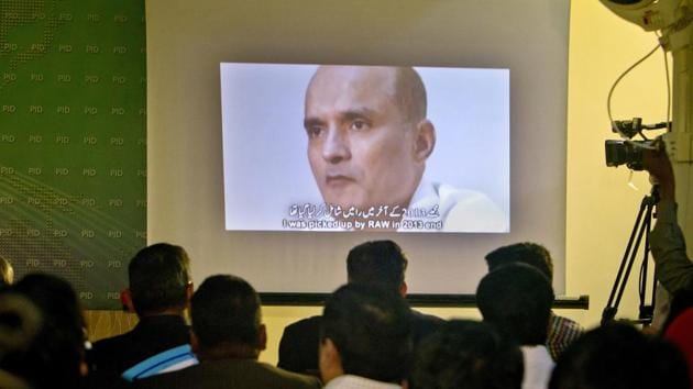 In this March 29, 2016 photo, journalists look at an image of Indian naval officer Kulbhushan Jadhav, who was arrested in March 2016, during a press conference by Pakistan's army spokesman. Security officials said the Pakistani army officer's abduction was aimed at pressuring Pakistan to release Kulbhushan Jadhav.(AP Photo)