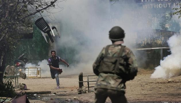 A Kashmiri student throws a chair on policemen in Srinagar, April 17. Kashmir was plunged into turmoil following the killing of the Hizbul leader Burhan Wani. Wani died in July 2016; for weeks afterwards, protesters and police battled it out across the Valley.(AP)