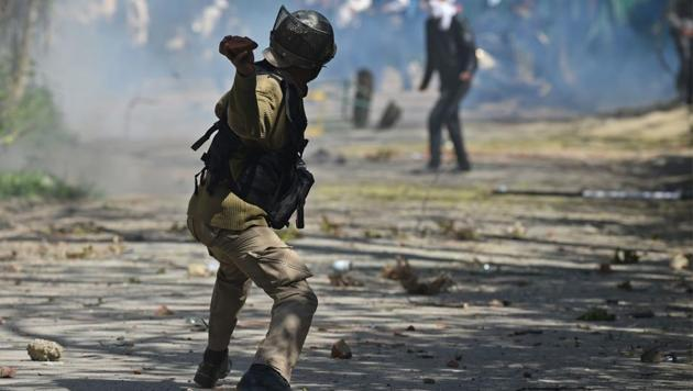 A security personnel throws a stone towards protesters during clashes near a college in central Srinagar's Lal Chowk.(AFP File Photo)