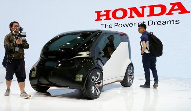 People gather around a Honda concept car displayed at Shanghai Auto Show during its media day.